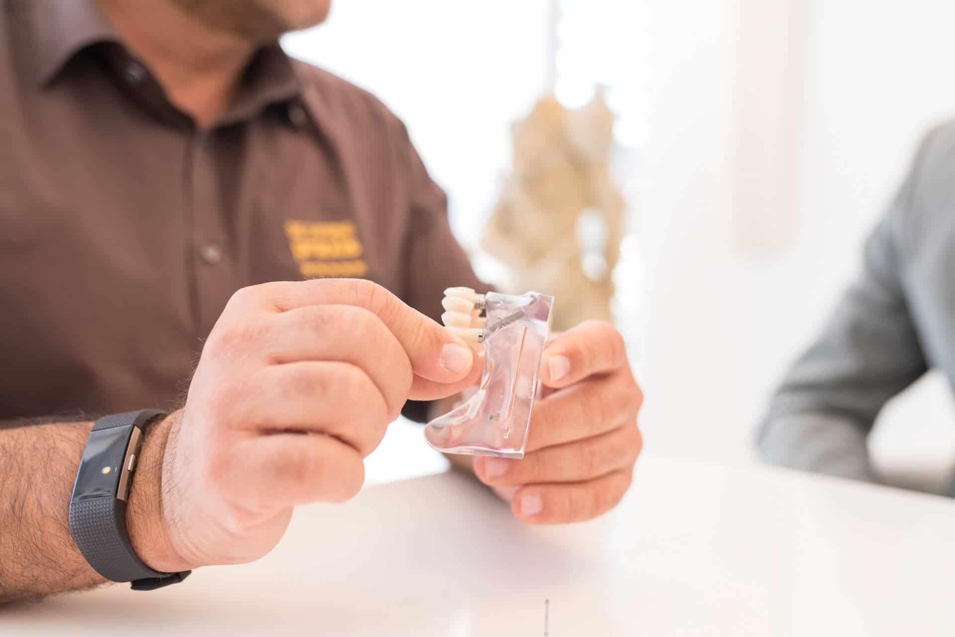 Zusehen sind die Hände vom Zahnarzt Dr. Gal, der Zahnimplantate in den Händen hält