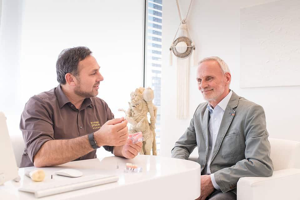 ZahnarzZahnarzt Dr. Gal sitzt mit einem Patienten im Bestprechungsraum Talk Room