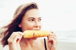 Junge Frau beisst genussvoll in einen Maiskolben und freut sich, dass sie keine lockenen Zähne hat