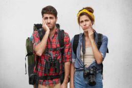 Backpacking Pärchen mit Rucksäcken, Fernglas und Kamera ausgestattet, halten jeweils eine Hand an Ihre Backen und überlegen, ob sie bei Zahnschmerzen im Urlaub ausreichend versichert sind