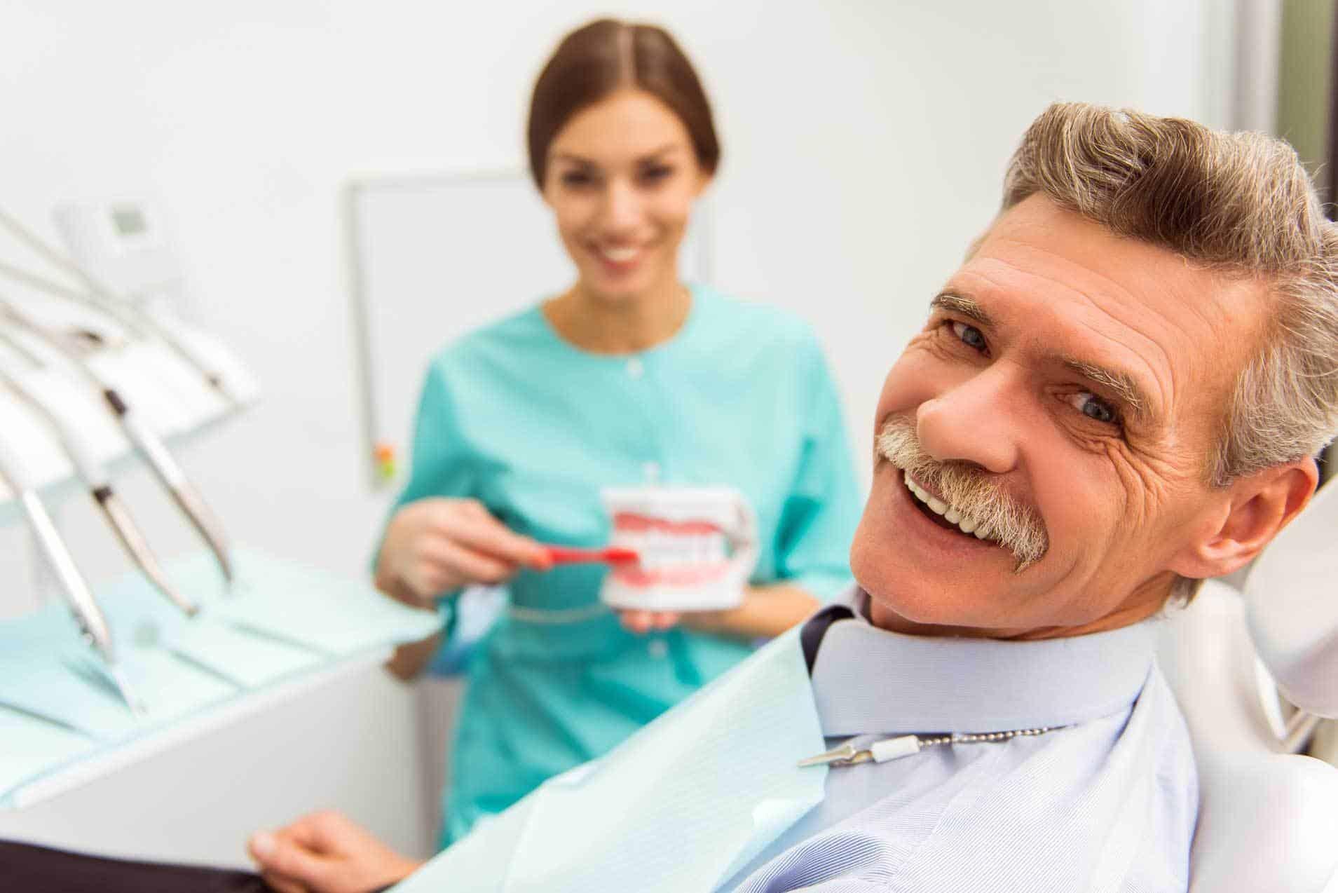Im Vordergrung lächelder Patient mittleren Alters im Zahnarztstuhl sitzend, wartet auf seine Behandlung feste Zähne sofort,im Hintergrund eine Helferin, mit einem Gebiss und einer Zahnbürste in der Hand