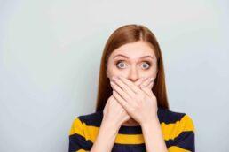 Junge Frau mit blau gelb gestreiftem Pulli hält sich beide Hände vor den Mund, da sie ihren schlechten Atem verdecken möchte