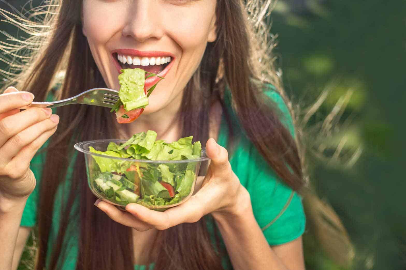 Junge Frau mit langen braunen Haaren hält eine kleine Glasschüssel mit Salat in der linken Hand und führt mit der rechten Hand eine Gabel Richtung Mund, sie macht sich Gedanken über den Einfluss von Ernährung auf die Zähne