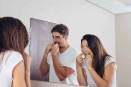 Pärchen steht im Bad vor dem Spiegel und beide säubern ihre Zähne mit Zahnseide