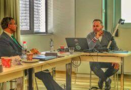Zahnarzt Dr. Jos Gal sitzt mit Gutachter im Besprechungsraum, Laptop und Getränke stehen auf dem Tisch