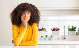 Junge dunkelhäutige Frau mit gelbem Pulli stützt ihren Kopf mit der rechten Hand und macht sich Gedanken über Zahnerkrankungen