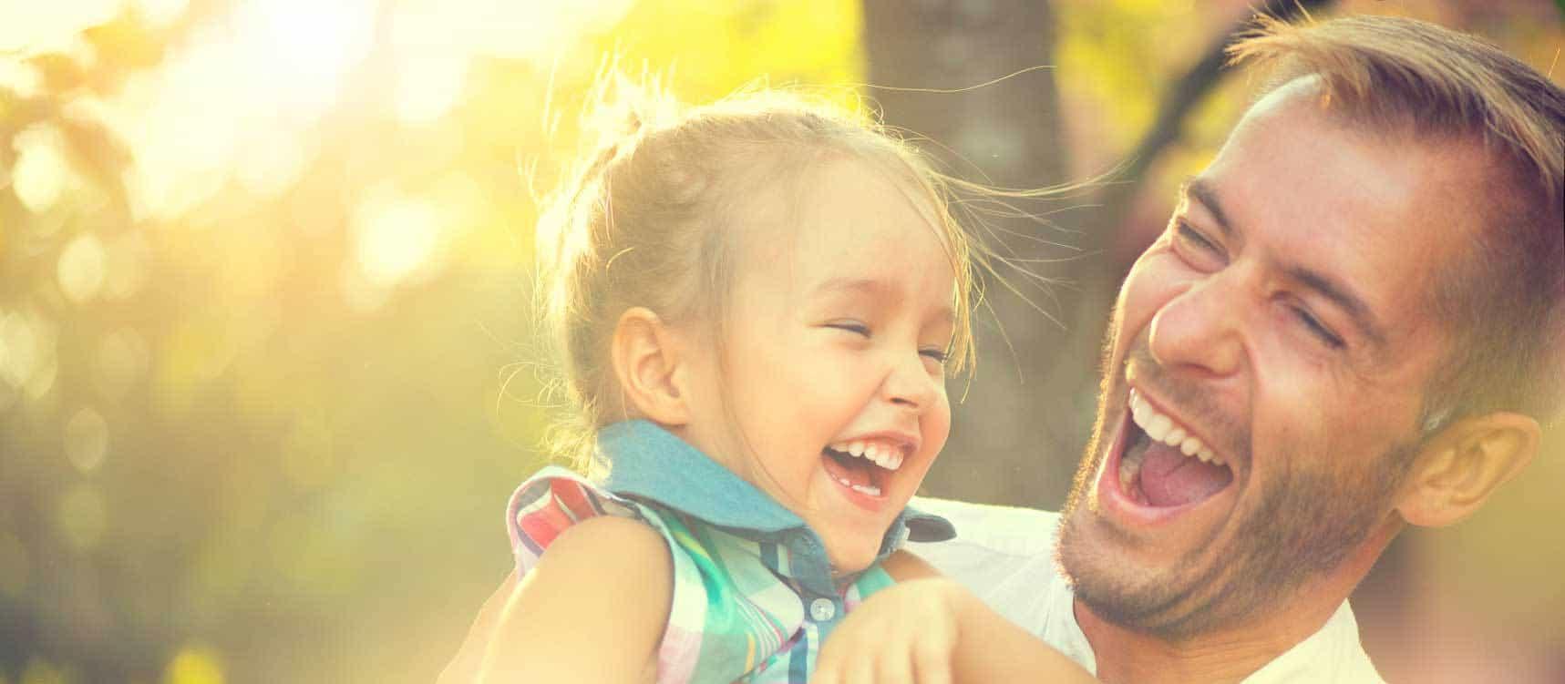 Vater mit kleiner Tochter im Arm kommen gerade lachend vom Zähne versiegeln, im Hintergrund ist Wald