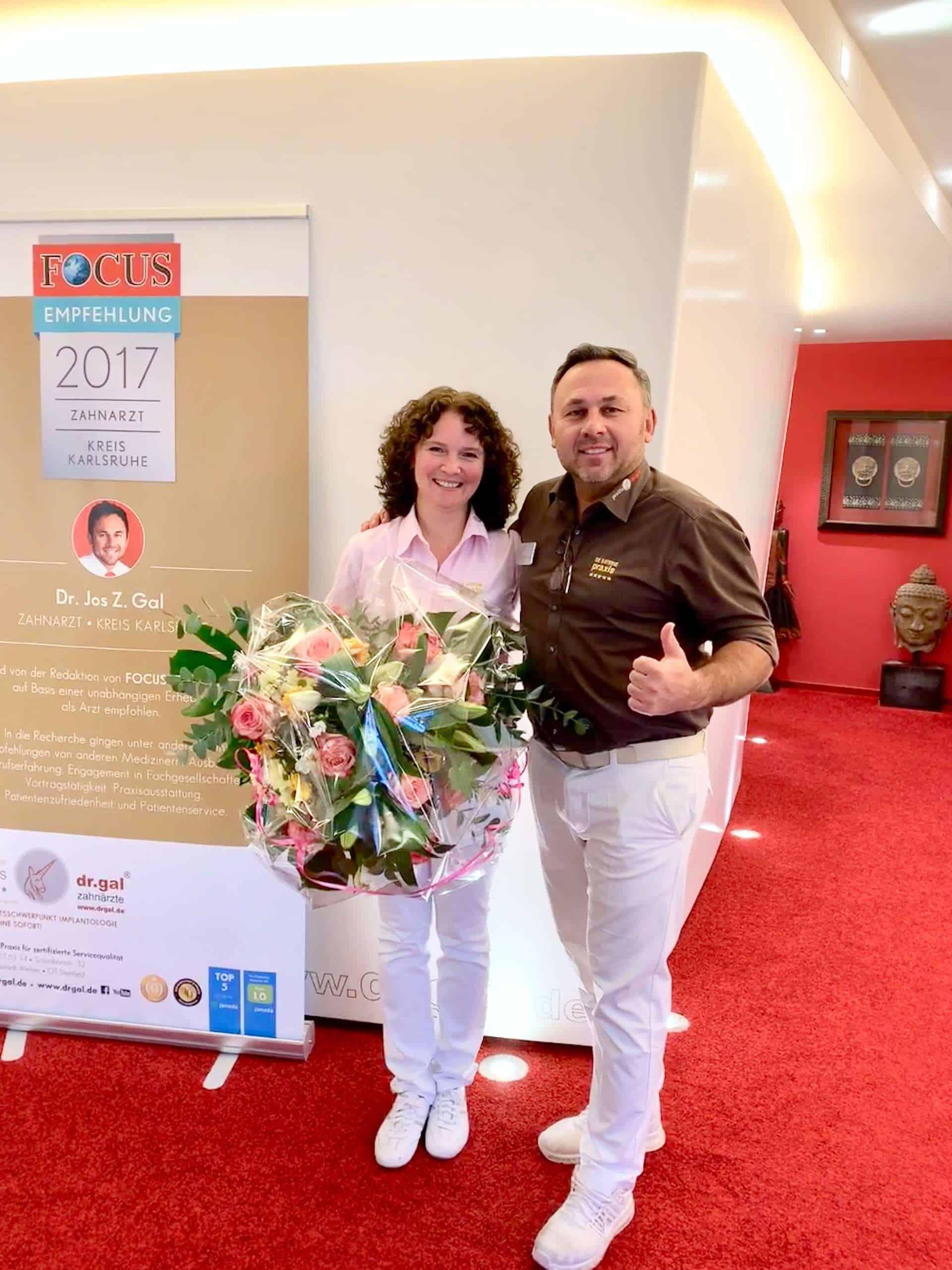 Zahnarzt Dr. Gal gratuliert Katharina Lenz mit Blumenstrauß zum Jubilaeum