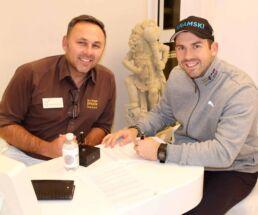Zahnarzt Dr. Gal und Golf-Pro Allen John sitzen an einem Stehtisch und Allen unterschreibt die offizielle Partnerschaft