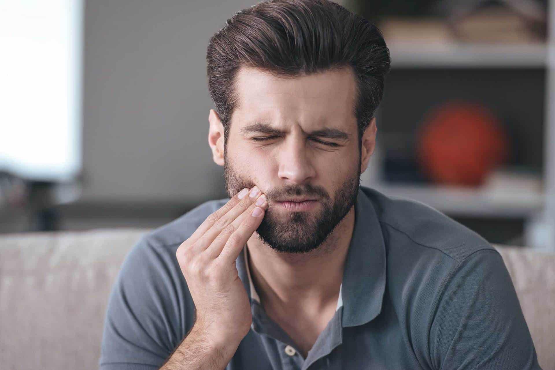 Junger Mann mit Bart hält sich die rechte Hand an die Backe, das Gesicht schmerzverzehrt vom pochenden Zahn