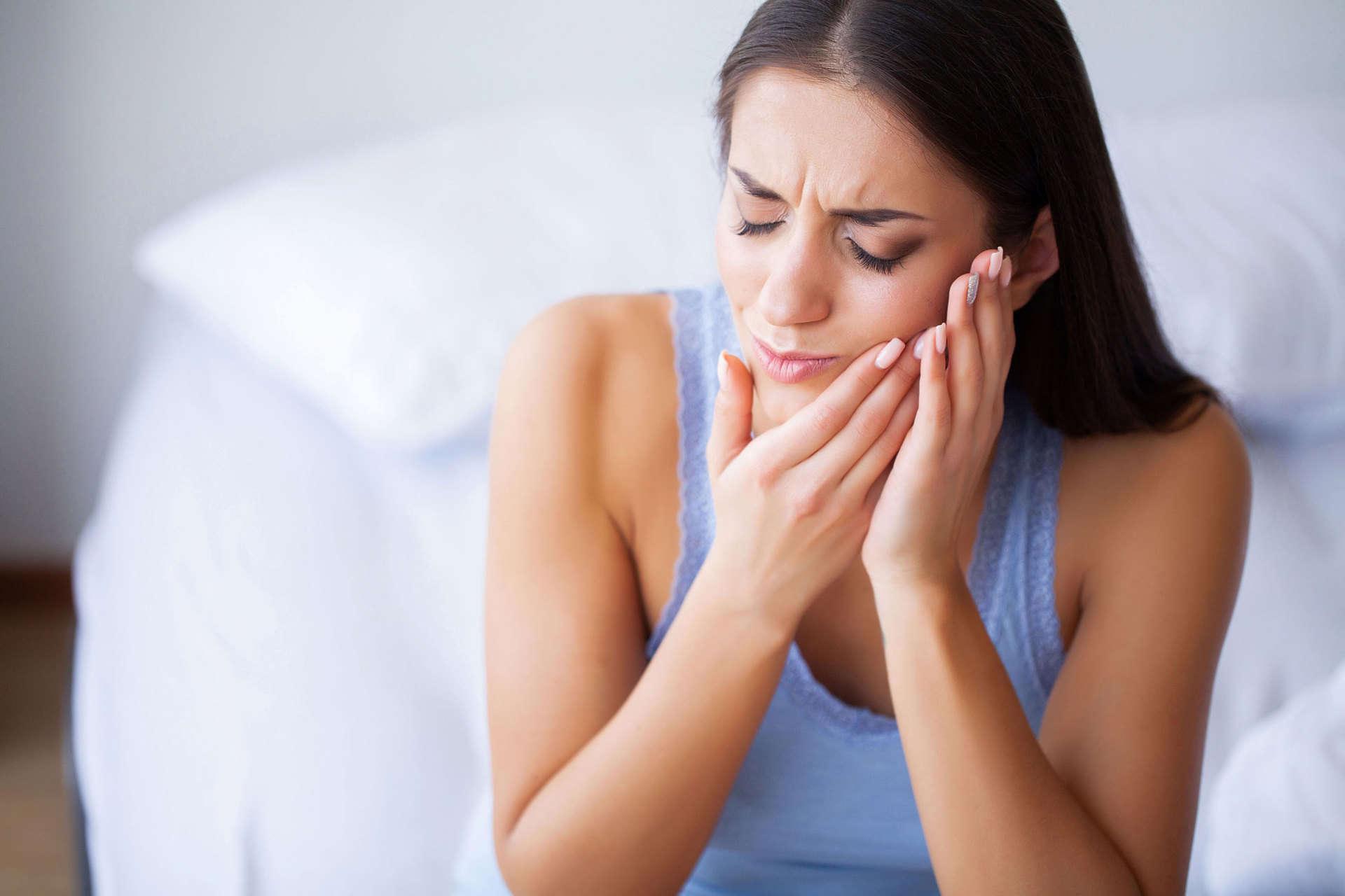 Junge Frau hält sich vor Schmerzen beide Hände an die linke Backe und überlegt, ob ein Zahnarztbesuch notwenig ist