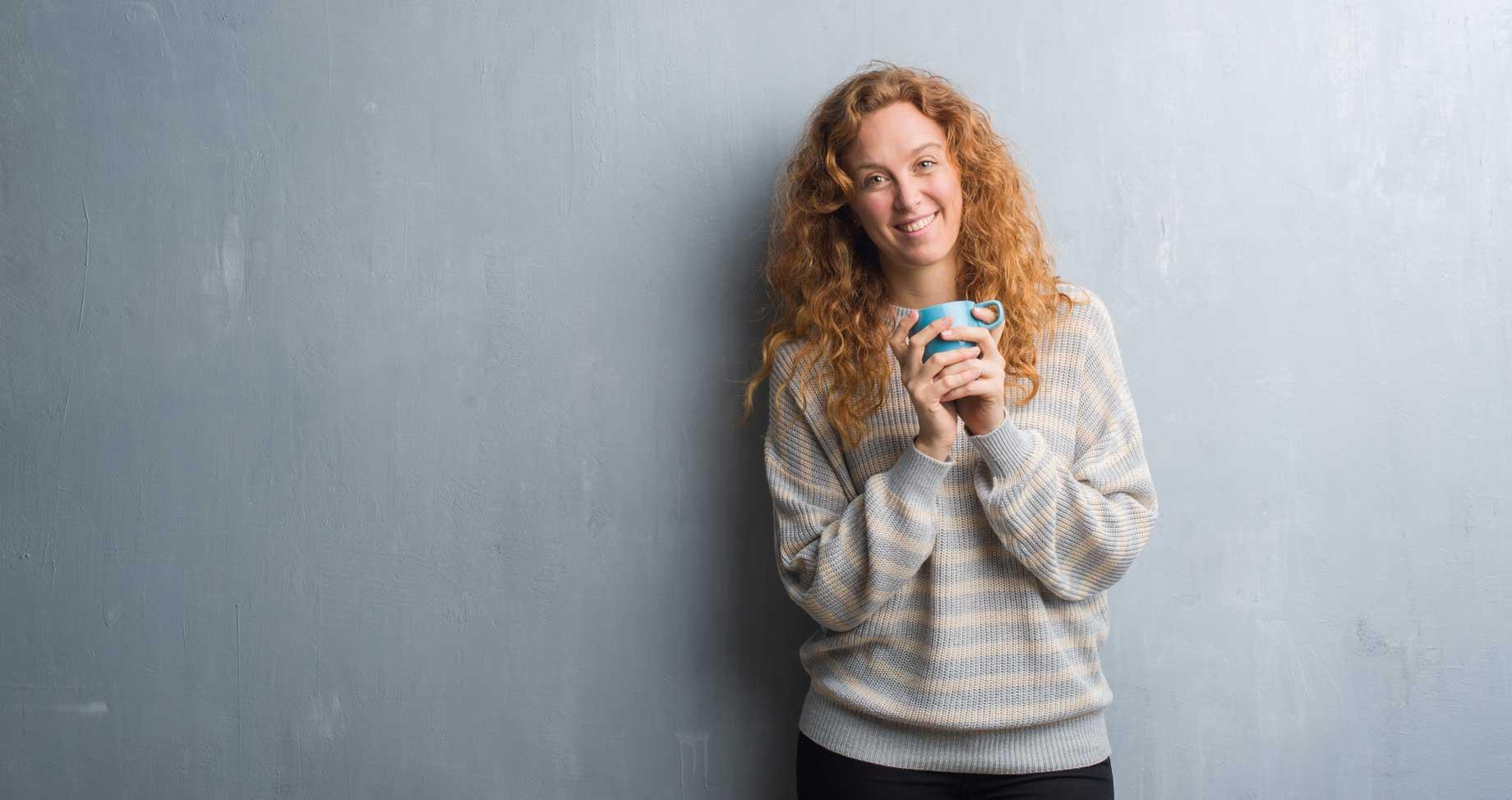 Junge Frau steht vor einem grauen Hintergrund und hält eine Tasse mit antibakteriellem Nahrungsmittel in der Hand