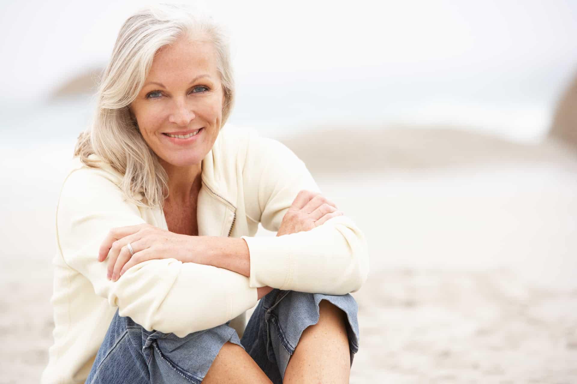 Frau mittleren Alters sitzt lächelnd am Strand und freut sich über ihre neuen festen Zähne