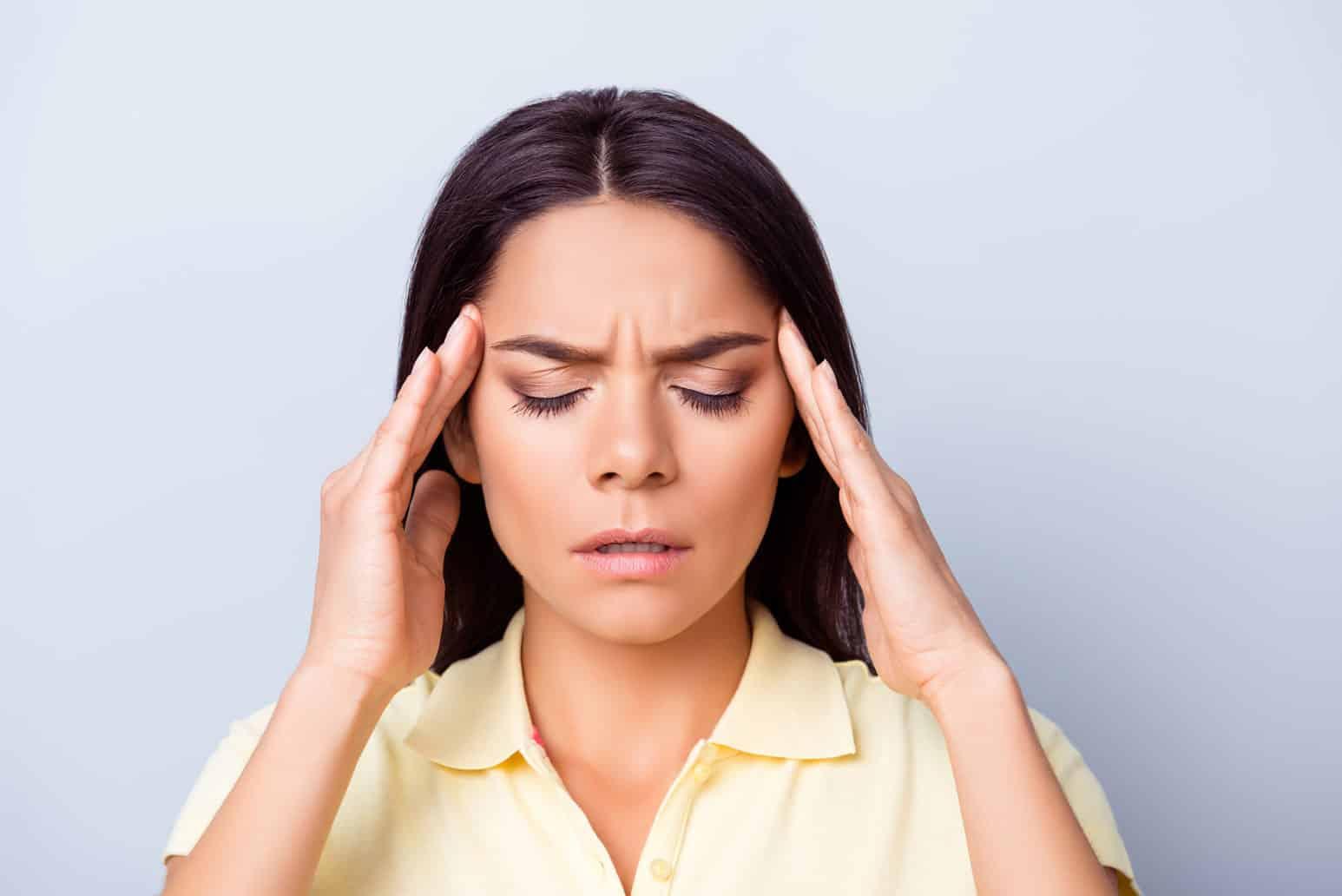 Junge Frau hat schmerzverzehrtes Gesicht durch Migränge und hält sich beide Hände an Ihre Schläfen.