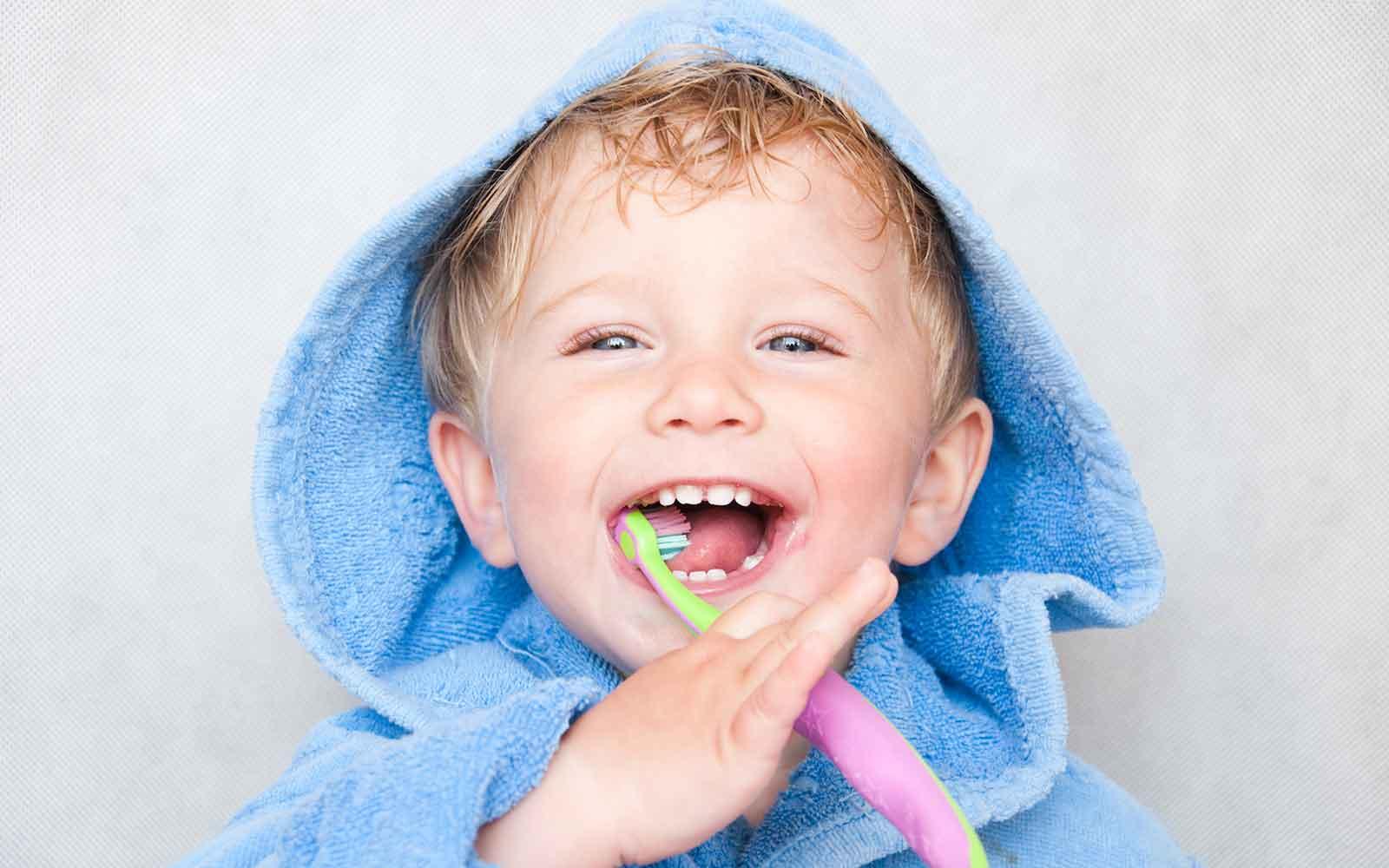 Kleiner Junge hat eine blaues Handtuch über dem Kopf und hält eine Zahnbürste in den Mund
