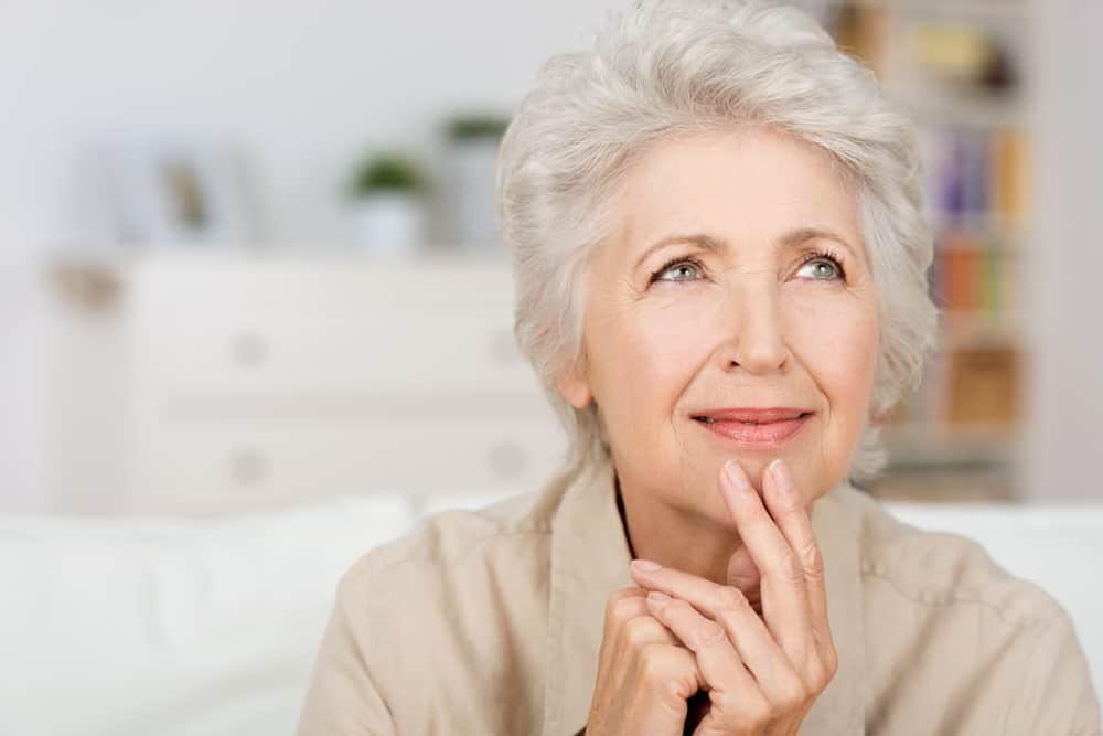 Frau Anfang 60 in Denkposition, hält zwei Finger ans Kinn