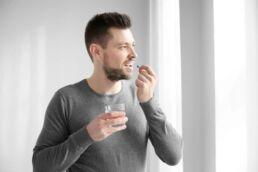 Mann hält ein Wasserglas in der rechen Hand und in der linken Hand hält er Medikamente der Zahnmedizin, die er zum Mund führt