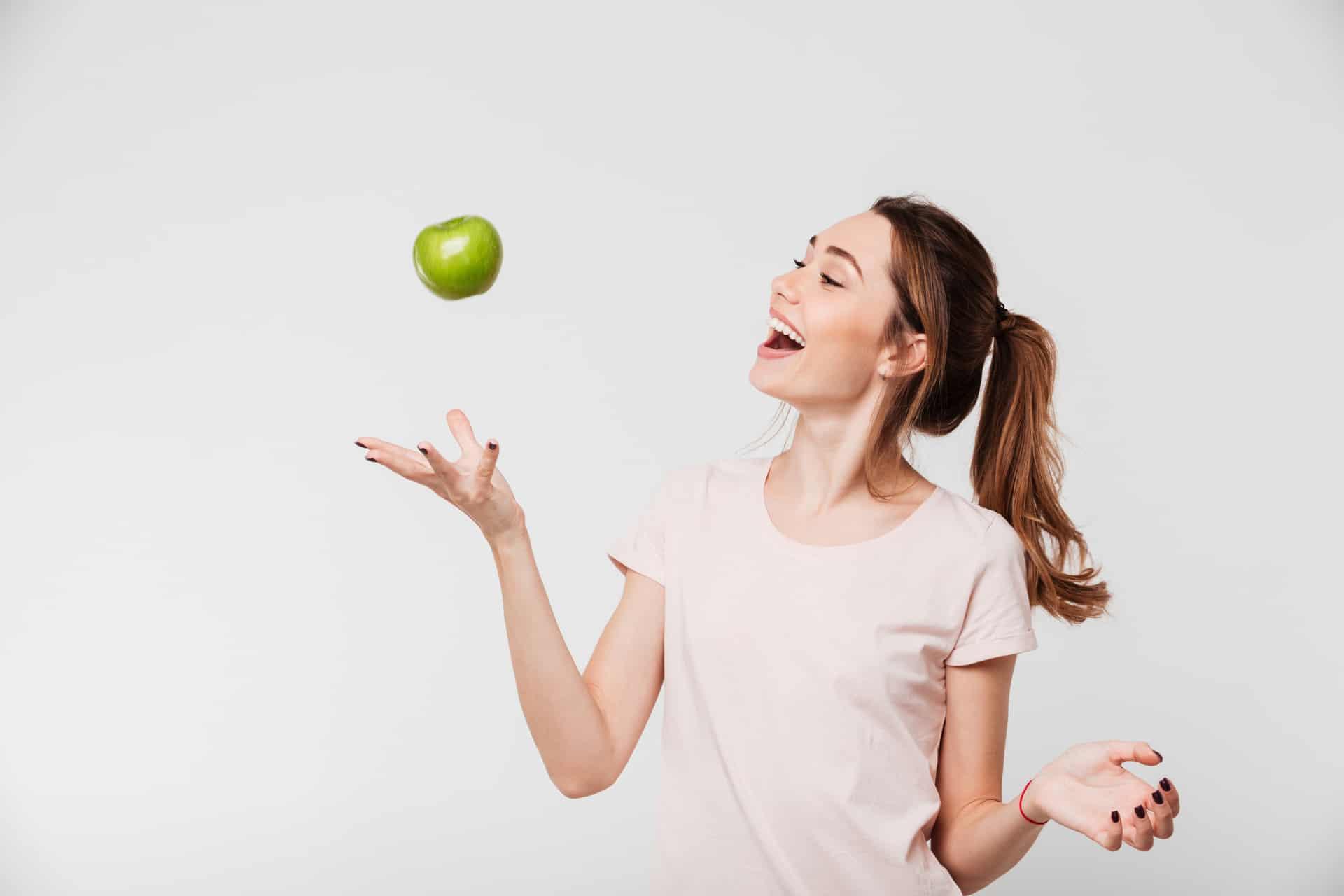 Junge Frau freut sich und wirft Apfel in die Luft, da ihre Zahnfleischentzündung durch optimale Ernährung verschwunden ist