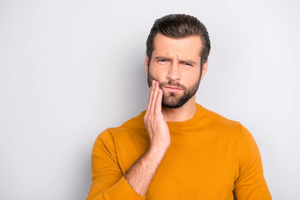 Junger Mann hält seine Hand an die schmerzende Backe, weil sein Zahnfleisch zurück geht