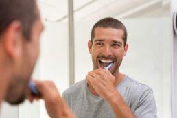 Junger Mann schaut in den Spiegel und probiert die Zahnpflege für Raucher aus.