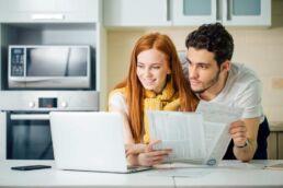 Ehepaar in der Küche, das sich Gedanken über die Zahnzusatzversicherung macht und Unterlagen vergleicht
