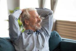 Ein entspannter, lächelnder Mann, der neue feste Zähne an nur einem Tag erhalten hat