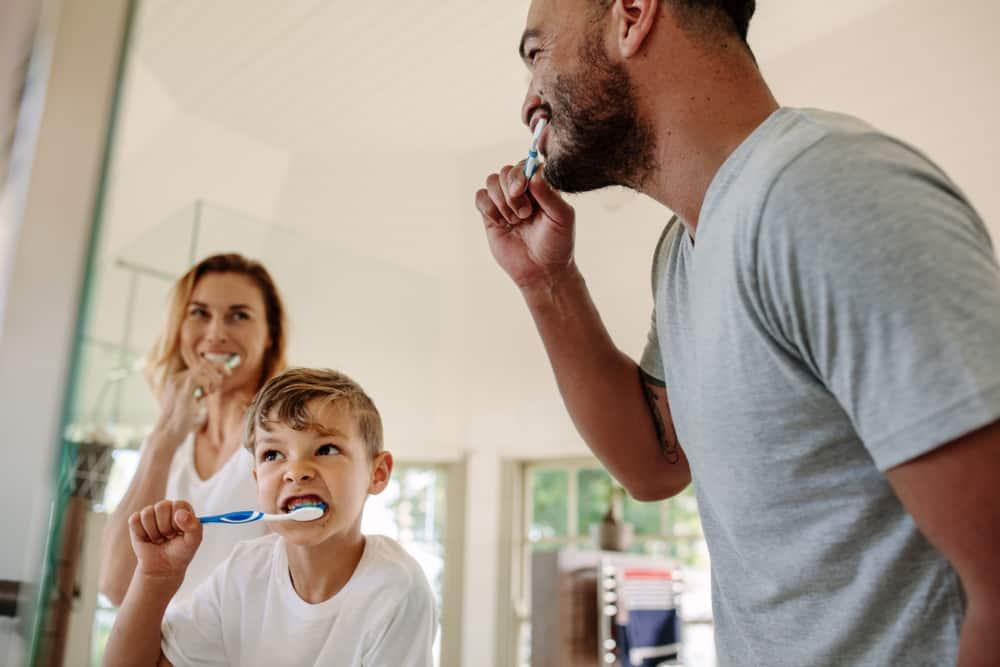 Glückliche Familie beim Zähneputzen, einem wichtigen Teil der Vorsorge
