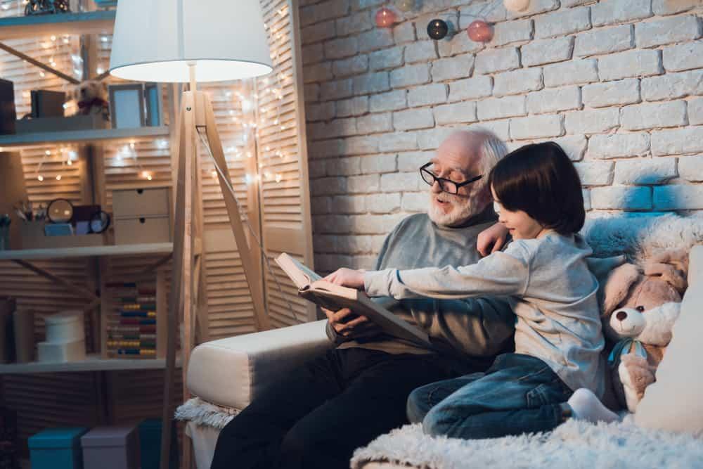Opa und Enkel lesen ein Buch über Märchen und Mythen. Davon gibt es auch bei der Zahngesundheit eine Menge.
