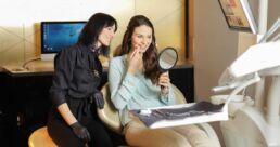 Zahnarzthelferin erklärt Frau die Begriffe beim Zahnarzt
