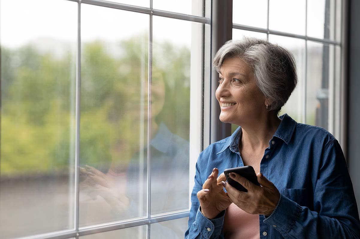 Ältere Frau steht mit dem Handy in der Hand am Fenster und überlegt, ob sie trotz Corona ihren Prophylaxe-Termin wahrnehmen sollte.
