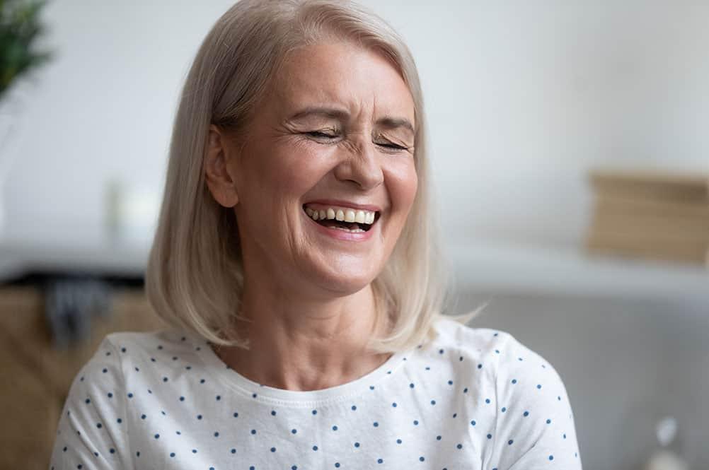 Lachende ältere Frau mit geraden Zähnen – vielleicht Zahnimplantate?
