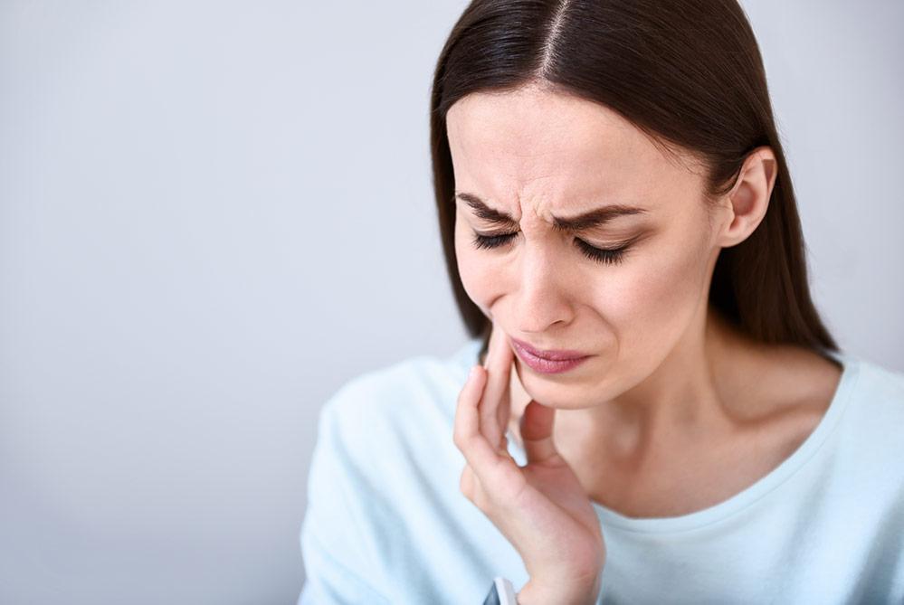 Frau greift sich mit verzerrtem Gesicht an die Wange – vielleicht bereitet ihr eine Zahnfüllung Schmerzen?