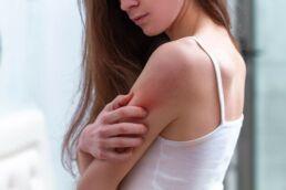 Junge Frau kratzt sich am Arm – Hautbeschwerden können oftmals im Zusammenhang mit verschiedenen Zahnerkrankungen stehen.