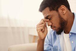 Junger Mann drückt sich mit angespanntem Gesicht auf den Nasenrücken. Auch ein gesunder Körper kann durch Zahnerkrankungen beeinträchtigt werden.
