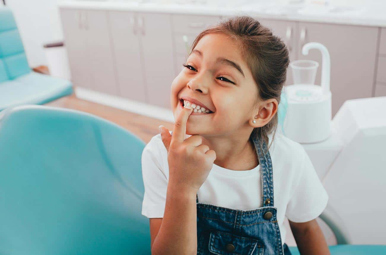 Ein Mädchen sitzt auf einem Behandlungsstuhl beim Zahnarzt und zeigt lächelnd auf seine sauberen Zähne.