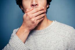 Mann, der sich die Hand über den Mund hält.