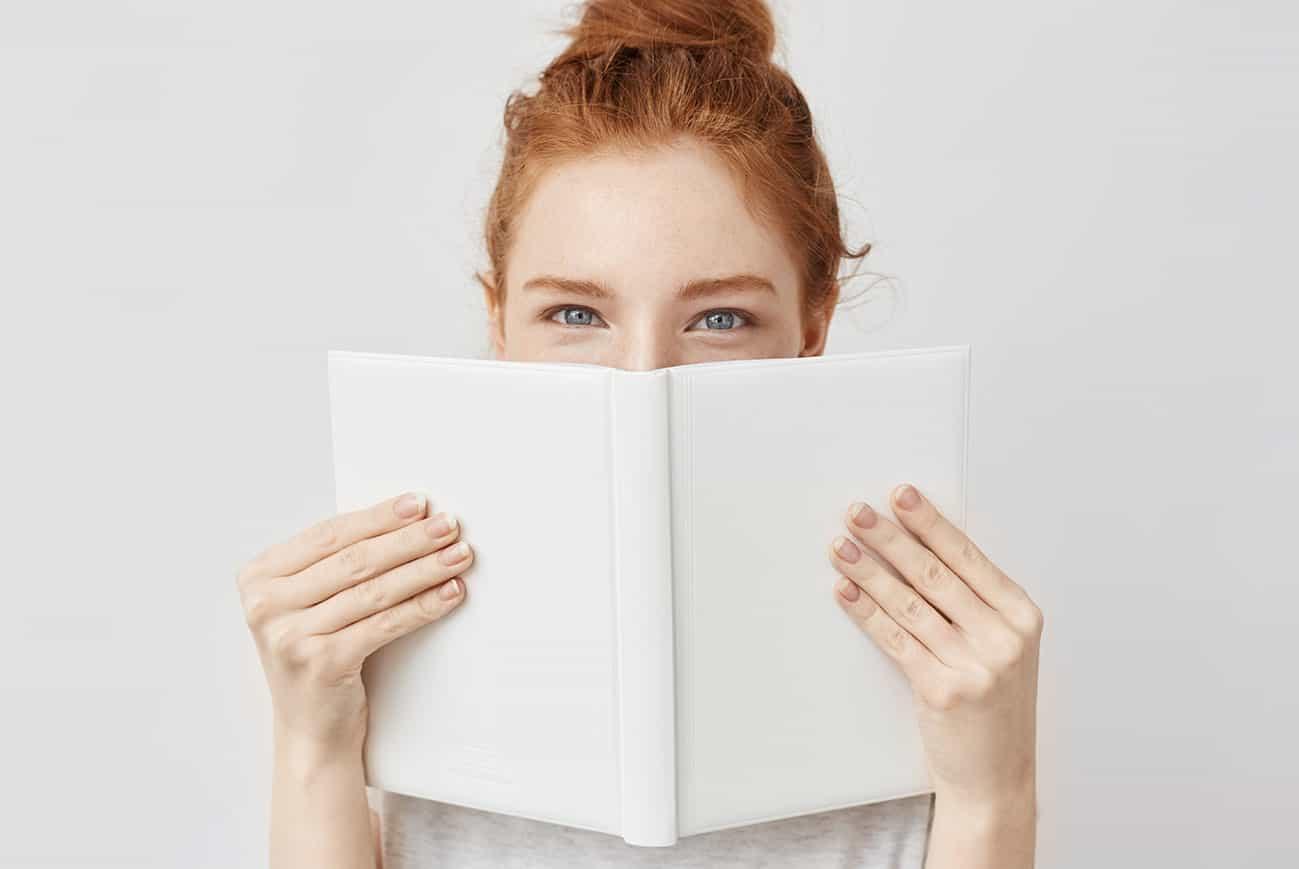 Junge Frau hält sich ein weißes Buch vors Gesicht, vielleicht um einen abgebrochenen Zahn zu verdecken.