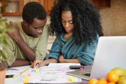 Junges Paar sitzt an einem Tisch mit Laptop und prüft zahlreiche Rechnungen.