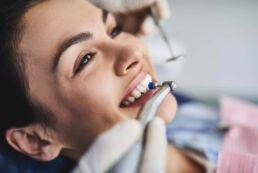 Eine lächelnde Frau bei der professionellen Zahnreinigung