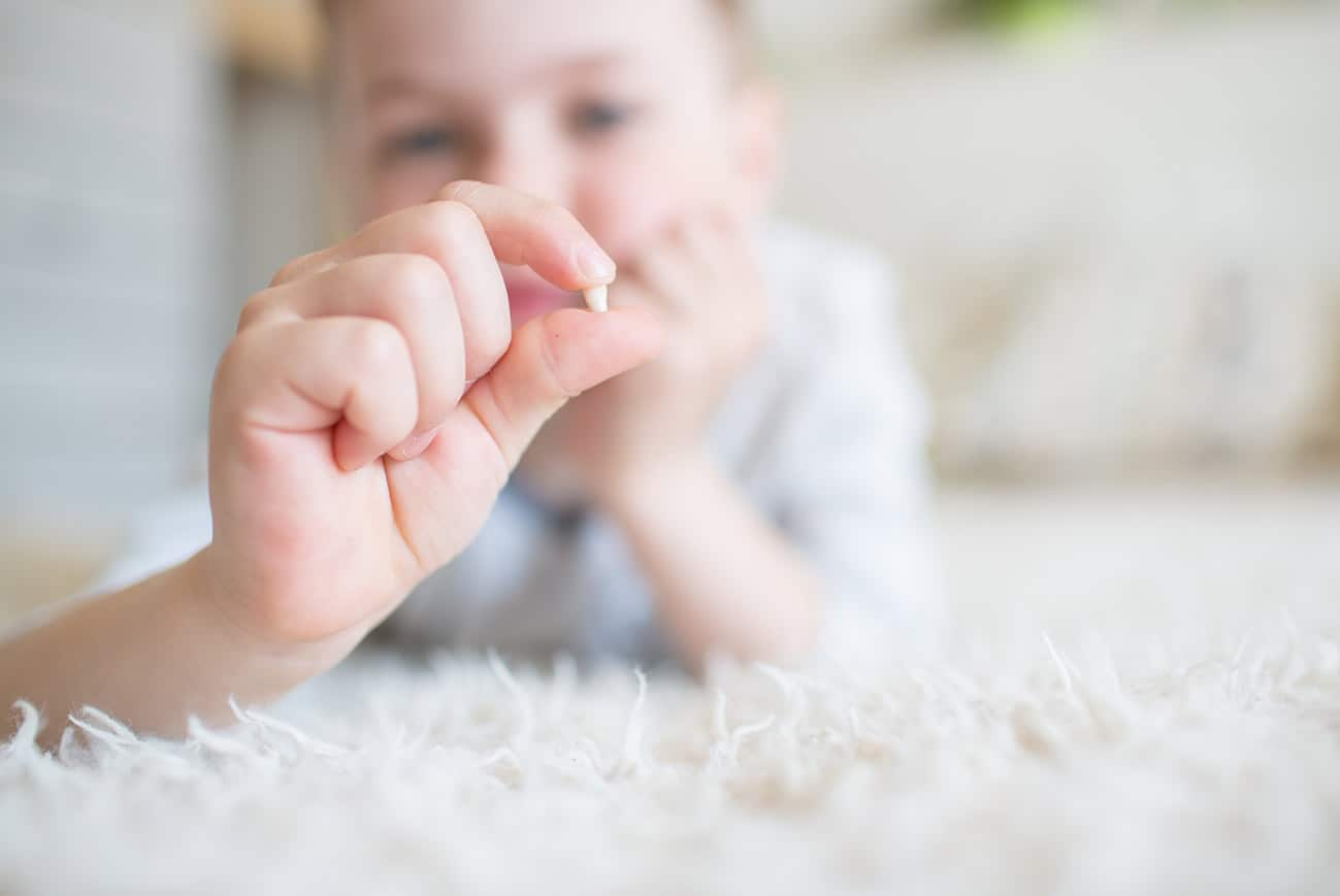 Ein Kind hält einen Milchzahn in die Kamera.