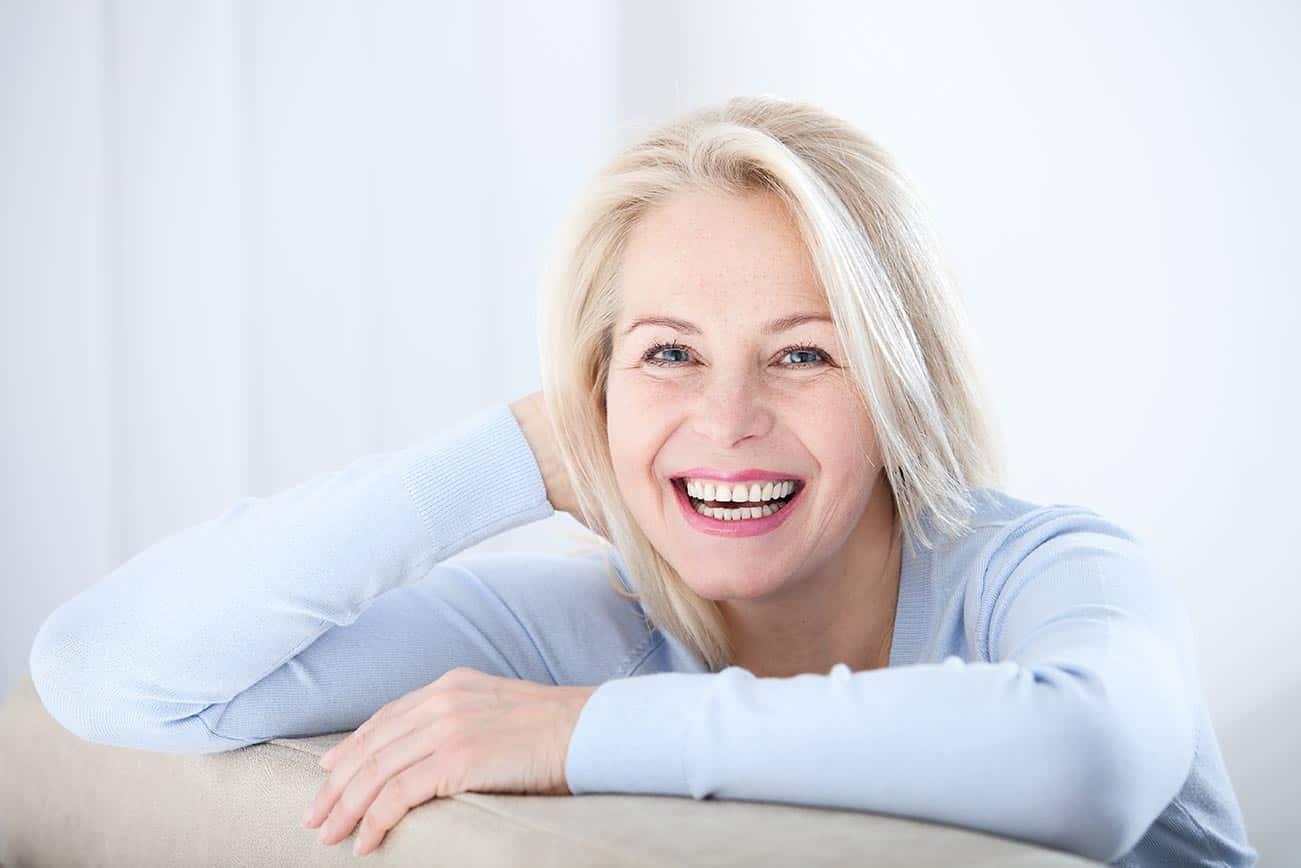 Ältere Frau mit hellblauem Pullover, die mit den Armen auf eine Sofalehne gestützt ist und lacht